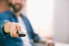 Casual man watching tv on his sofa. At home in the living room Royalty Free Stock Photos