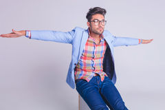 Casual man wearing glasses, seated on chair. With arms wide open while looking away from the camera Royalty Free Stock Images