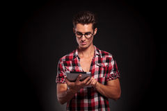 Casual man wearing glasses using a tablet Royalty Free Stock Photography