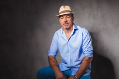 Casual man wearing a hat seated in studio background posing Royalty Free Stock Images