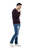 Casual man wearing jeans, sweater and sunglasses walking and looking down Royalty Free Stock Photo