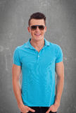 Casual man wearing sunglasses and polo shirt. Young casual man wearing sunglasses and polo shirt on a gray concrete background Royalty Free Stock Photos