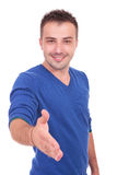 Casual man welcoming you with a handshake Royalty Free Stock Image