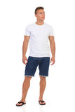 Casual Man In White T-shirt And Jeans Shorts Looking Away. Handsome young man in white shirt, jeans shorts and black sandals is standing and looking away. Front Stock Images
