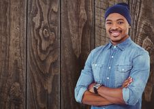 Casual man with wooly hat standing on ahead a wood wall. Digital composite of Casual man with wooly hat standing on ahead a wood wall Royalty Free Stock Images