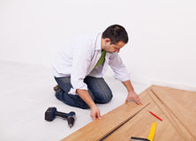 Casual man or worker installing flooring. Home improvemant - worker installing laminate flooring Royalty Free Stock Photos
