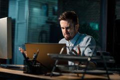 Man having problems with electronics. Casual man working in office and looking super mad having problems with malfunctioning laptop in office Stock Images