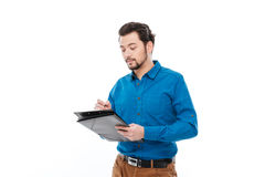 Casual man writing something in clipboard Stock Photo