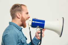 Casual man yelling into megaphone Royalty Free Stock Image