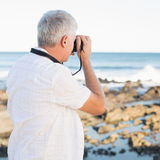 Casual mature man taking a photo of the sea Royalty Free Stock Photography