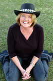 Casual mature woman. Smiling mature woman wearing a cowboy hat and sitting in the grass Royalty Free Stock Image