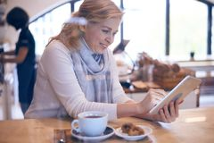 Casual mature woman working on tablet in cafe Stock Images