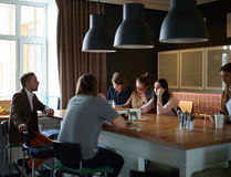 Casual Meeting of Young Team. Young creative team dressed in business casual having briefing meeting at kitchen isle table in modern office space Stock Photo