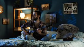 Playful couple singing with guitar on bed stock photo