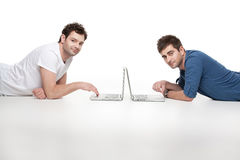 Casual men lying in front of laptops Stock Photos