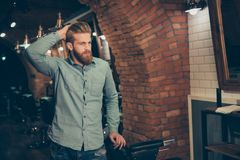 Casual men`s life. Perfect! Harsh stylish red bearded man in a b. Arber shop. His hairstyle is spectacular and so trendy! He is severe and very confident royalty free stock images