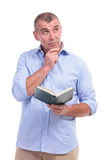 Casual middle aged man with book, thinks Royalty Free Stock Images