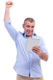 Casual middle aged man cheering with pad Stock Photos