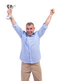 Casual middle aged man cheers with trophy Stock Image