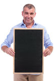 Casual middle aged man holding chalkboard Stock Photo