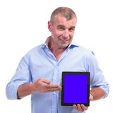 Casual middle aged man presenting tablet Stock Images