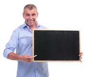 Casual middle aged man presents blackboard Stock Photo
