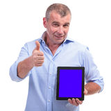 Casual middle aged man recommends a tablet Royalty Free Stock Photo