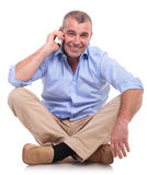 Casual middle aged man sits and chats on phone Stock Photos