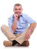 Casual middle aged man sits pensive. Casual senior man sitting on the floor with his legs crossed and holding his hand at his chin, in a pensive way, while Stock Photo