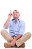 Casual middle aged man sits and points up Royalty Free Stock Images