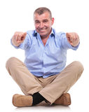 Casual middle aged man sits and points at you Royalty Free Stock Images