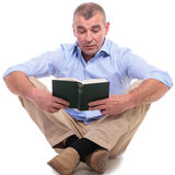 Casual middle aged man sits and reads book Royalty Free Stock Images