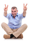 Casual middle aged man sits and shows victory Stock Photos