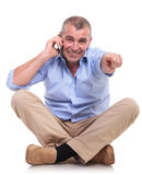 Casual middle aged man sits talks and points Royalty Free Stock Photo