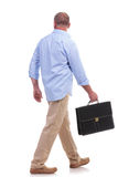 Casual middle aged man walks with suitcase Royalty Free Stock Images