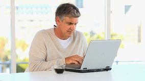 Casual middle aged man working on a laptop stock footage
