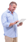 Casual middle aged man working on tablet Stock Images