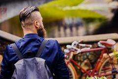 Modern guy with backpack. Back view. royalty free stock images