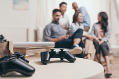 Casual multiethnic friends sitting on sofa with joysticks on foreground Royalty Free Stock Photo