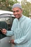 Casual muslim calling. Success casual entrepreneur calling near by his car in muslim costume Stock Photo