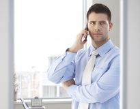 Casual office worker talking on mobile phone Royalty Free Stock Photography