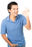 Casual OK Hand Gesture Latino Male Smiling Left. Hispanic male wearing casual clothes, blue shirt smiling warmly, showing OK left hand sign expressing good Stock Image