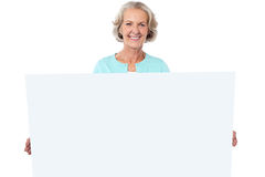 Casual old lady holding a blank billboard Royalty Free Stock Photography
