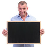 Casual old man holds a blank blackboard Royalty Free Stock Image