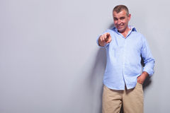 Casual old man points at you with hand in pocket Stock Photo