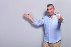 Casual old man presents and shows ok sign Stock Photography