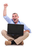 Casual old man sits and cheers with laptop Royalty Free Stock Photography
