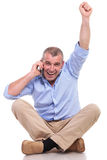 Casual old man sits and cheers while on phone Stock Image