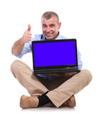 Casual old man sits, holds laptop and ok sign Royalty Free Stock Image