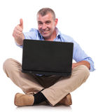 Casual old man sits with laptop and shows ok Stock Photography